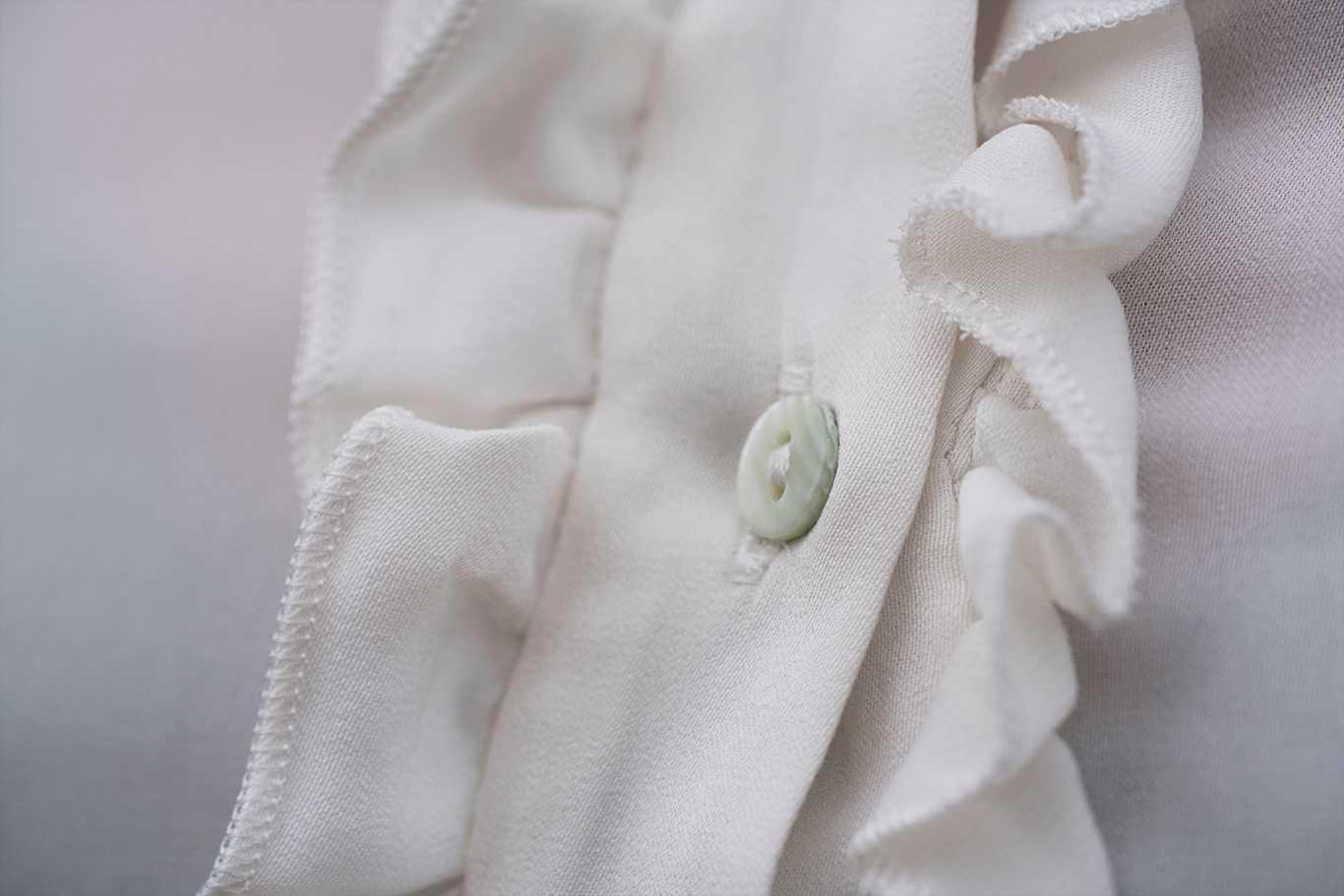 Detalle del pecho de camisa blanca mango